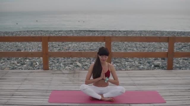 kvinnan meditates i naturen. - endast unga kvinnor bildbanksvideor och videomaterial från bakom kulisserna