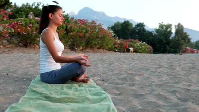 Woman meditates in the morning on the seashore video