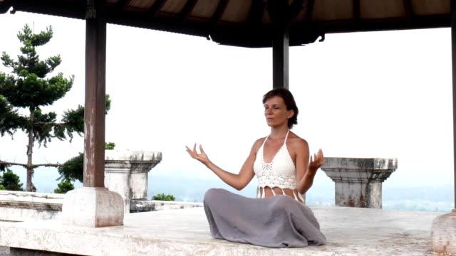vídeos de stock, filmes e b-roll de mulher meditando e fazendo yoga no templo abandonado. pose de praticante feminina - sounion