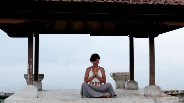 kvinna meditera och göra yoga i övergivna tempel - india statue bildbanksvideor och videomaterial från bakom kulisserna