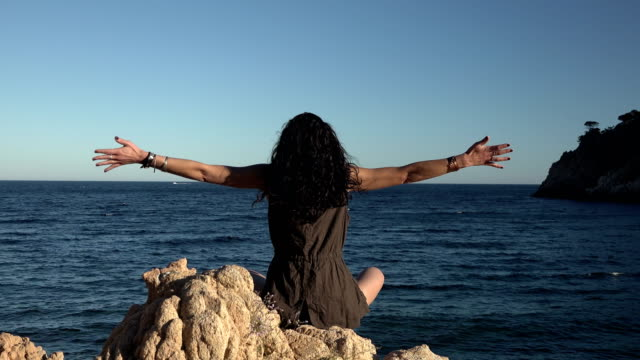 woman meditating and doing yoga on a cliff by the beach - mindfulness stock videos & royalty-free footage