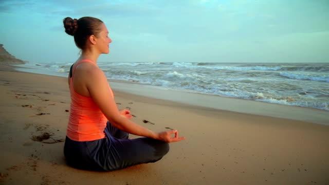 Woman meditating at beach video