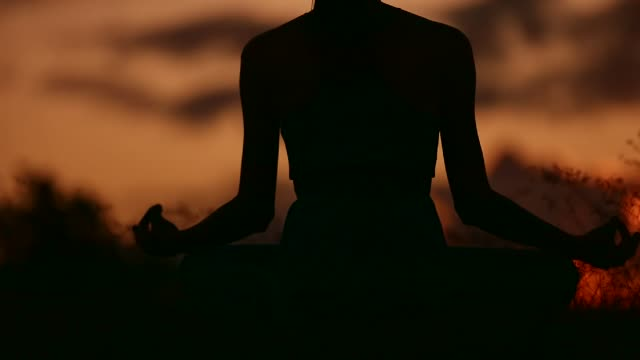 Woman meditating at sunset. Woman meditating in a grass field at sunset. lotus position stock videos & royalty-free footage