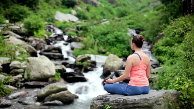 Woman meditating at tropical waterfall in Lotus pose Padmasana video