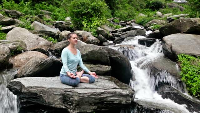 Woman meditating at tropical waterfall video