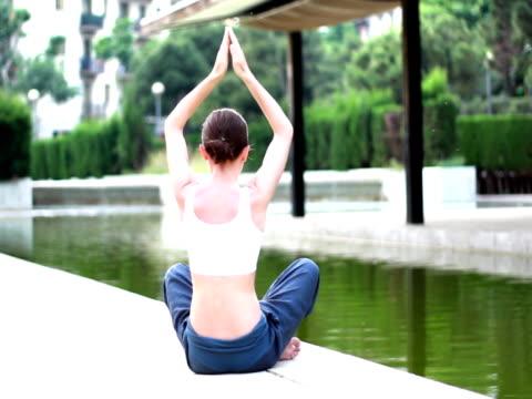 woman meditating by the water in park - i̇nsan sırtı stok videoları ve detay görüntü çekimi