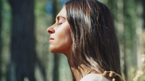 kobieta medytująca w lesie - piękno filmów i materiałów b-roll