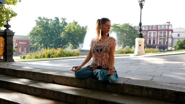 Woman meditating in lotus position on top of stairs. Young girl in blue pants doing yoga on busy city background. slow motion video