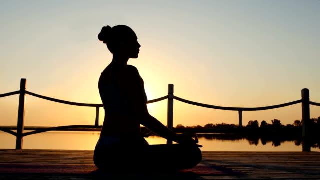 Woman meditating in pose lotus over orange sun video