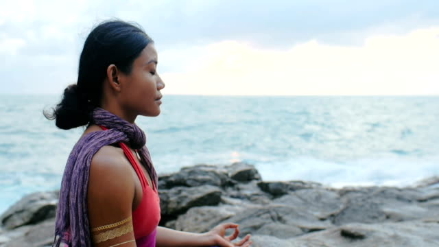 woman meditating in turkish pose sukhasana during yoga class on ocean outdoor - mudra video stock e b–roll
