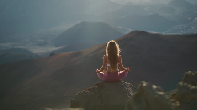일출에서 산 꼭대기에서 명상 하는 여자 - mindfulness 스톡 비디오 및 b-롤 화면