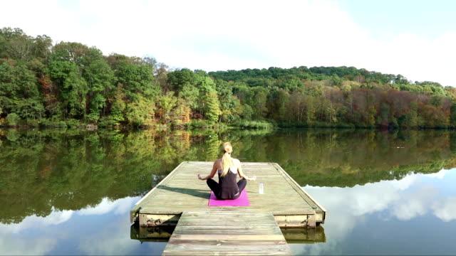 Woman Meditating On Boat Dock video