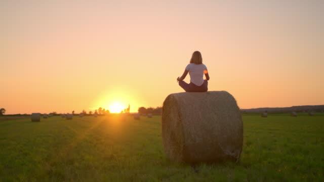 ms женщина медитирует на вершине тюка сена в идиллическом, сельское поле на закате - mindfulness стоковые видео и кадры b-roll
