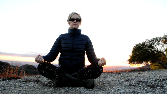 Woman Meditating on Top of Hill at Sunset video