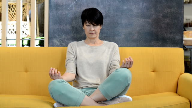 Woman Meditating on Yellow Couch Short haired caucasian woman 40, crossed legged on a yellow couch meditating. lotus position stock videos & royalty-free footage