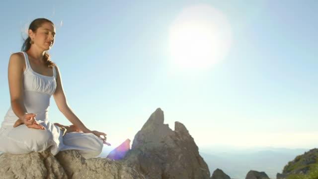 hd: woman meditating under the clear sky - lotusställning bildbanksvideor och videomaterial från bakom kulisserna