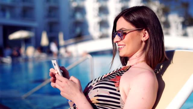 stockvideo's en b-roll-footage met vrouw overseinen met vrienden op haar smartphone - gebruind