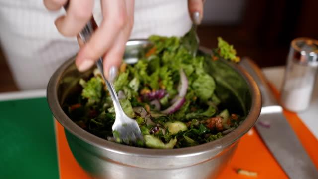 Woman mixes ingredients of vegetable salad in a bowl. Close-up of stirring vegetable salad in a bowl. Mix the ingredients of a vegetarian salad. Preparation of vegetable salad.