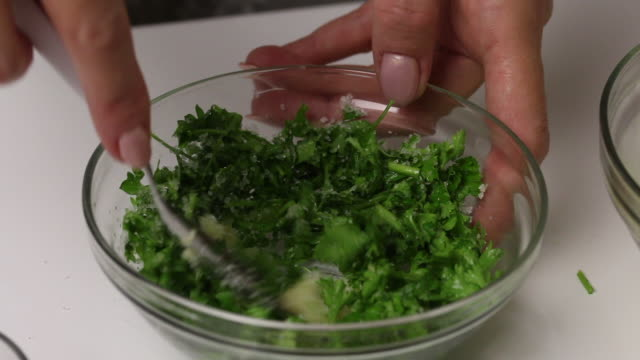 A woman mixes parsley, garlic and salt in a glass container. Salted lard with herbs and spices.