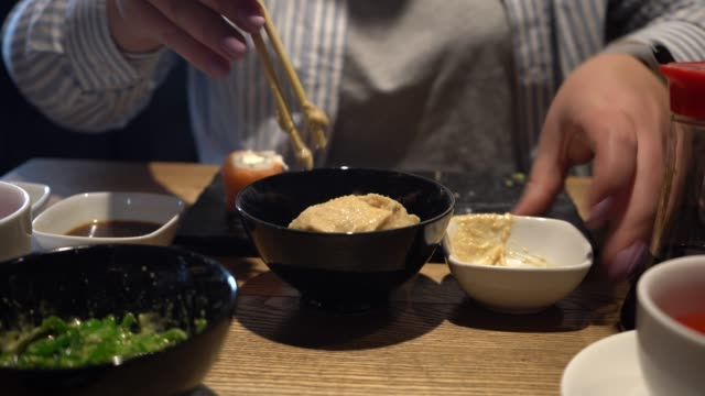 woman mixes seaweed sauce and salad with wooden chopsticks. close-up. chinese sticks mix seaweed salad with sauce. - sesamo video stock e b–roll