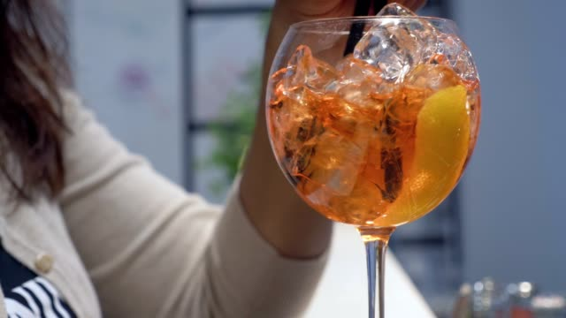 woman mixing her cocktail at bar counter- slow motion-close up woman mixing her cocktail at bar counter- slow motion-close up aperitif stock videos & royalty-free footage