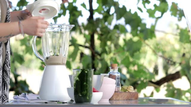 女性の健康的な緑のほうれん草のスムージー屋外を混合 - ローフード点の映像素材/bロール