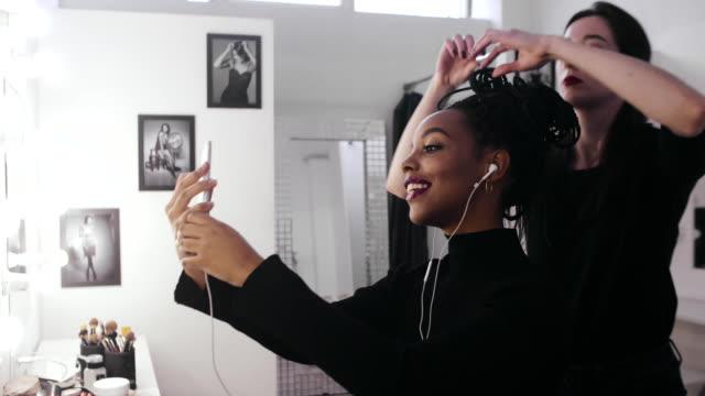 ビデオ通話用の携帯電話を使用してスタジオの女性モデル - 美容室のビデオ点の映像素材/bロール