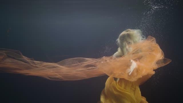 Woman model swimming like mermaid underwater pool on dark background