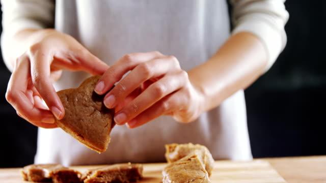 Woman molding gingerbread dough on wooden board 4k video