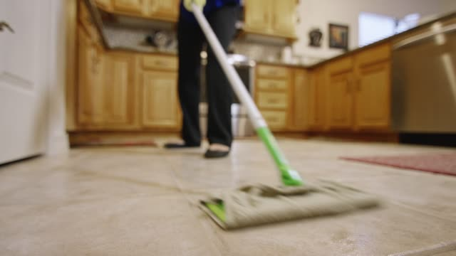 A Woman Mops the Floor of a Residential Kitchen