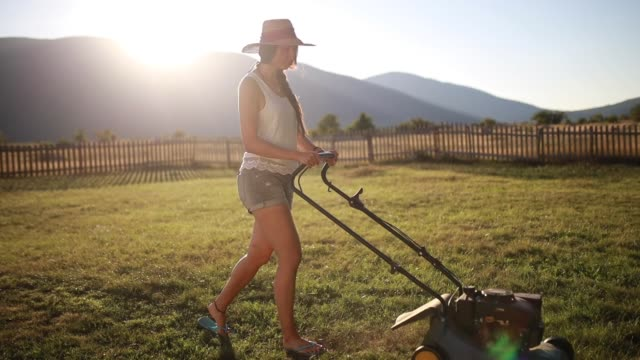Woman mowing the lawn during the quarantine