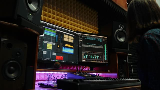 Woman musician mixing and mastering song at sound music studio with monitors and equalizer mixing gear on screen. Sound engineer creating pop song for new album. Female songwriter working at studio