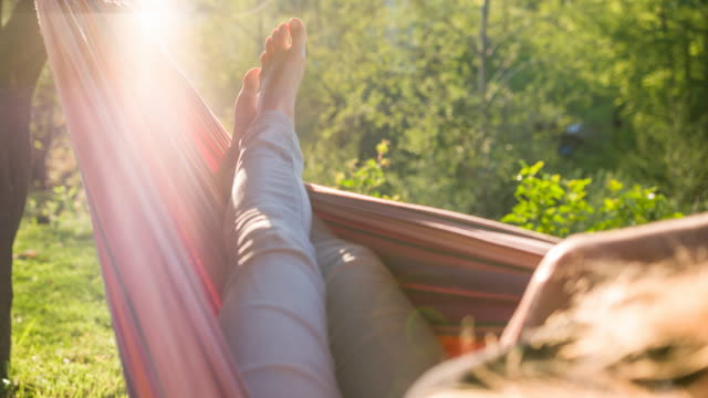 woman napping in a hammock, enjoying summer vacations - amaca video stock e b–roll