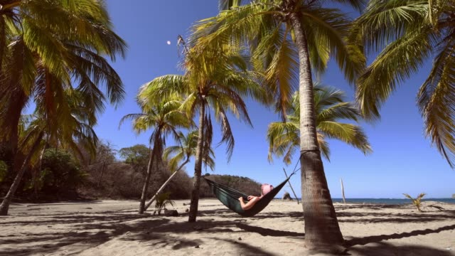 Woman napping on hammock under palm trees in Costa Rica video