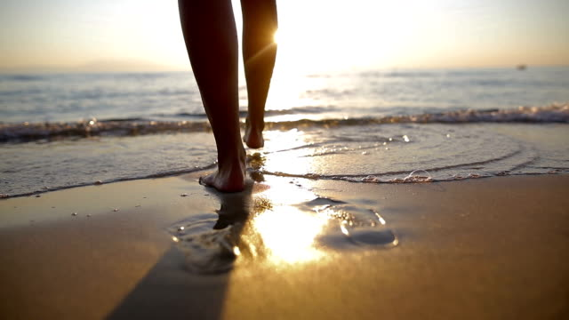 woman near the ocean.walking on the beach. footsteps in the sand - scalzo video stock e b–roll