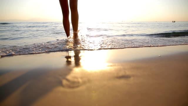 vídeos de stock, filmes e b-roll de mulher perto do oceano. caminhando na praia. pegadas na areia - férias na praia