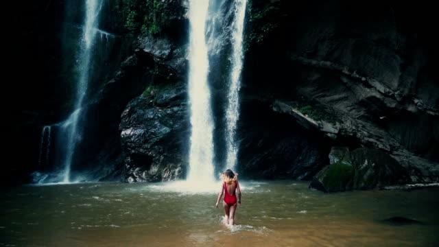 stockvideo's en b-roll-footage met vrouw in de buurt van de tropische waterfal - twilight