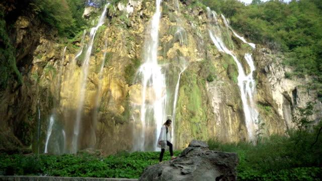woman near the waterfall - национальный парк плитвицкие озёра стоковые видео и кадры b-roll