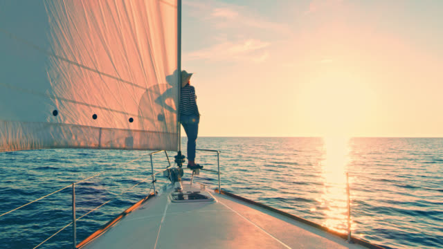 vídeos de stock e filmes b-roll de ws woman observing the sunset from a sailboat's bow - veleiro