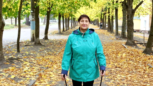 A woman of retirement age is practicing Nordic walking.
