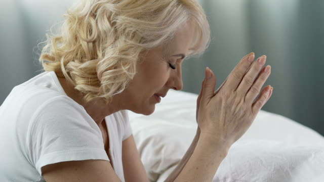 Woman of senior age praying at her bed, eyes closed, smiling, gratitude to God video