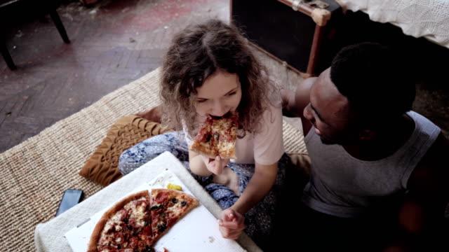 vídeos de stock, filmes e b-roll de mulher oferece pizza para o homem, mas comer a fatia sozinha. multirraciais casal se divertindo durante a refeição com fast-food - comida feita em casa