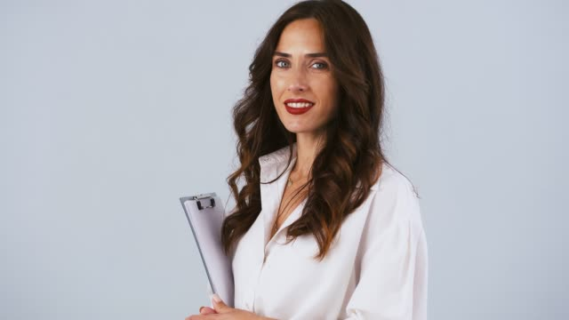 woman office worker in white shirt is holding black clipboard with sheets, looking at you and smiling. posing on gray background. close up - direttrice video stock e b–roll