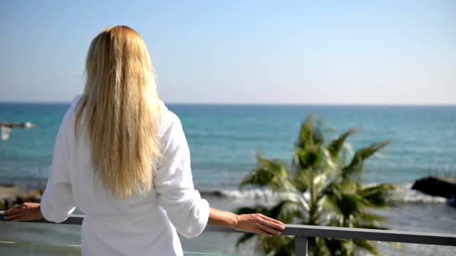kvinna på en balkong i morgonrock med havsutsikt - strandnära bildbanksvideor och videomaterial från bakom kulisserna