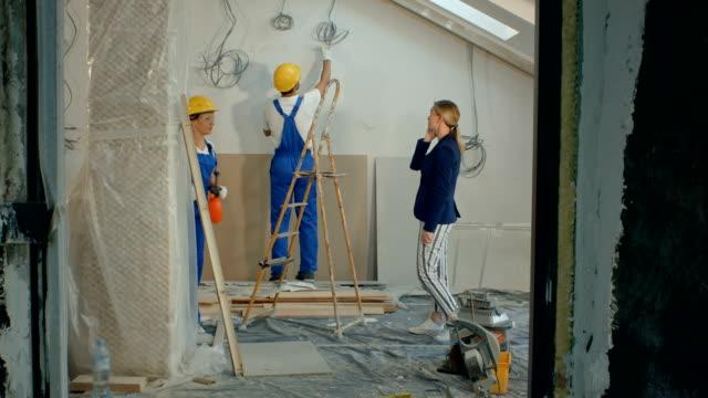 Vrouw op een gesprek met aannemers bespreken op bouwplaats video