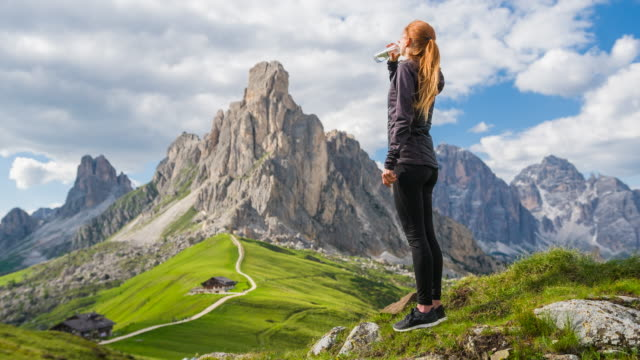 woman on a grass meadow drinking water, view of mountains in background - ritemprarsi video stock e b–roll