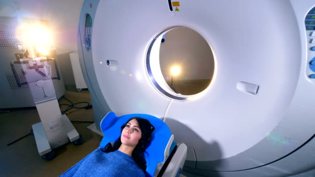 Woman on a magnetic resonance imaging MRI scan in a modern hospital. Magnetic resonance imaging (MRI) scanner in a modern hospital. 4K. tomography stock videos & royalty-free footage