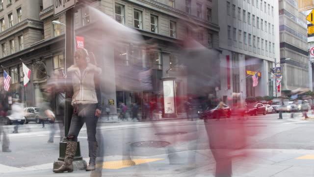 kvinna på en mobiltelefon med upptagna människor passerar ett downtown övergångsställe - stationär bildbanksvideor och videomaterial från bakom kulisserna