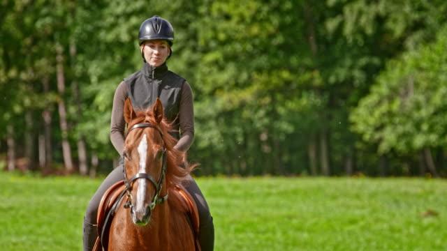 SLO MO femme sur une détente à cheval à travers l'alpage - Vidéo