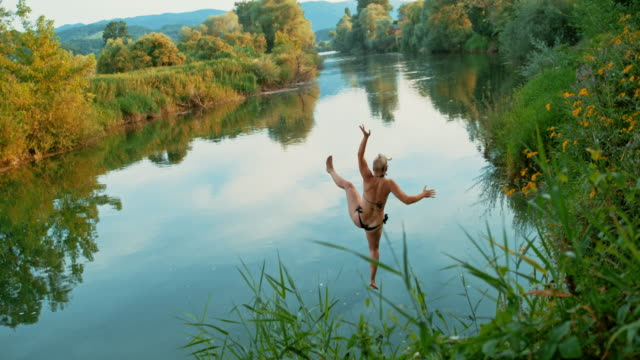 vídeos de stock e filmes b-roll de time warp woman on a rope swing jumping into the river - jump pool, swimmer